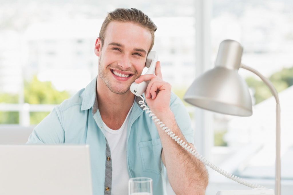customer service man smiling taking phone call